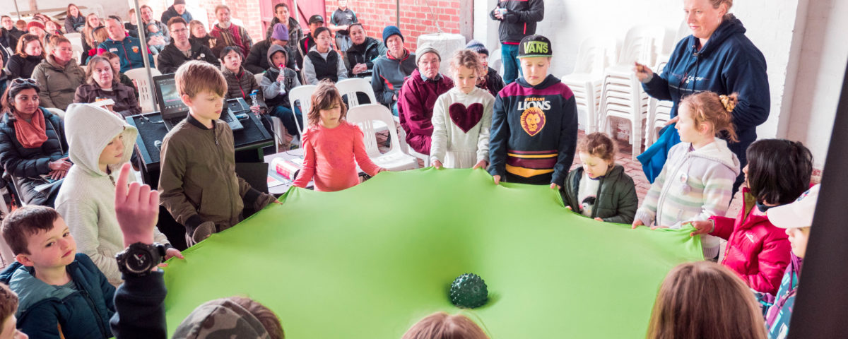 Children performing gravity simulation with a rubber sheet